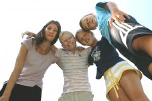Deux filles et deux garçons se tiennent en riant, en se tenant par les épaules. (Stephanie Hofschlaeger/pixelio.de)